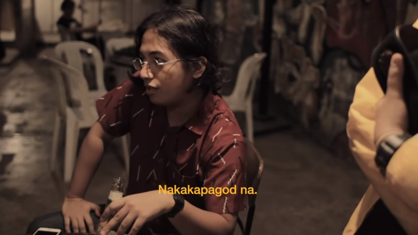 "screen capture from the Naubos Na music video linked later in the post. guy sitting on a chair talking. caption says ""Nakakapagod na."""