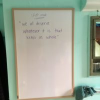 My new whiteboard against my light green wall. The whiteboard reads, in purple,