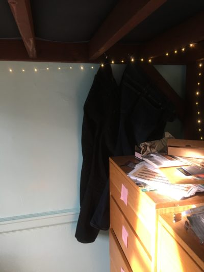 The corner of my room underneath my loft. Some clothes and fairy lights are hanging on hooks attached to the loft, and the sunlight lights up my dressers in the foreground.