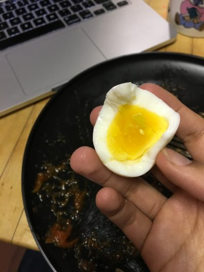 My hand holding half of a hardboiled egg.