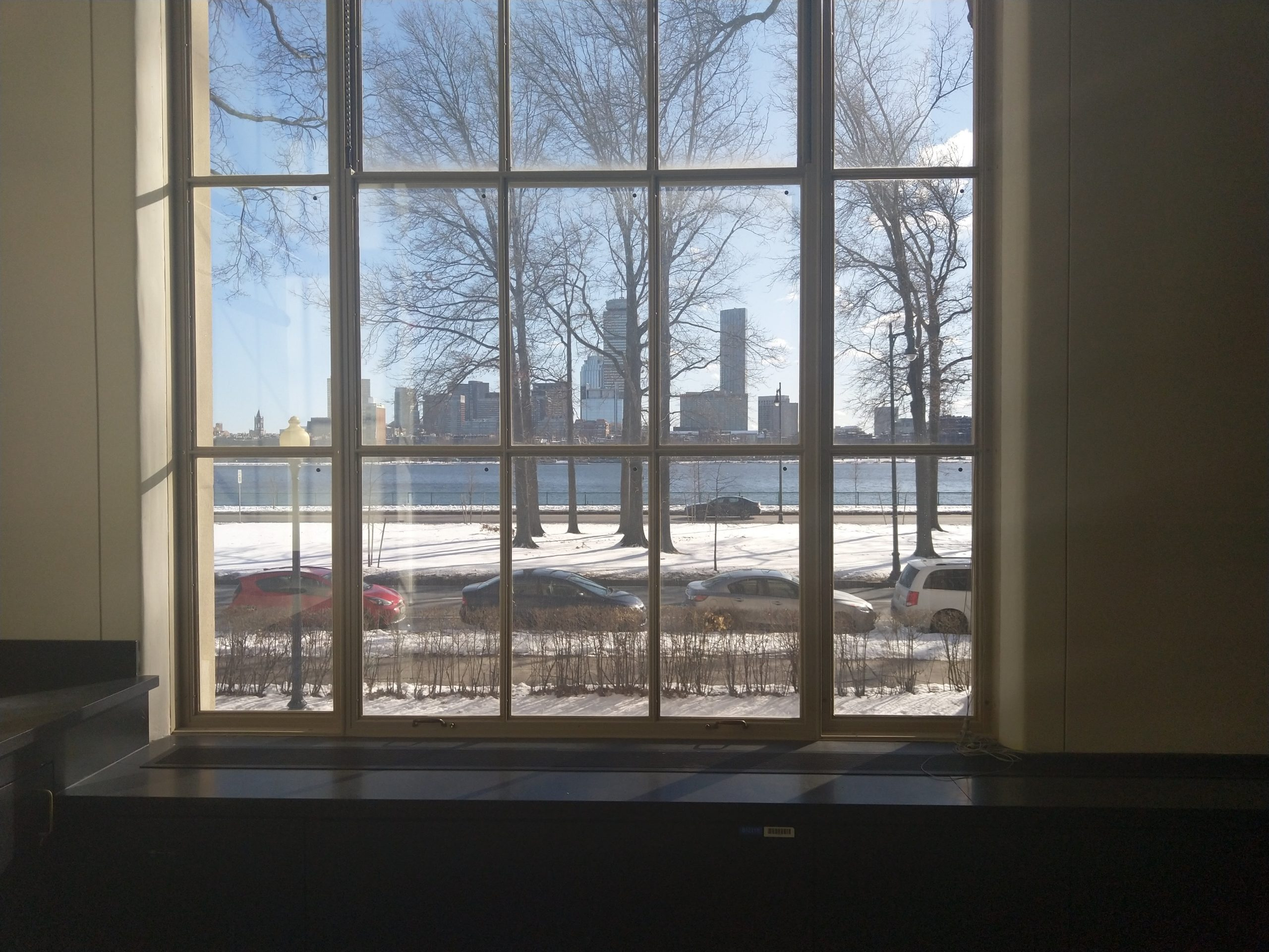 the view outside a window, with the river and the boston skyline in the distance