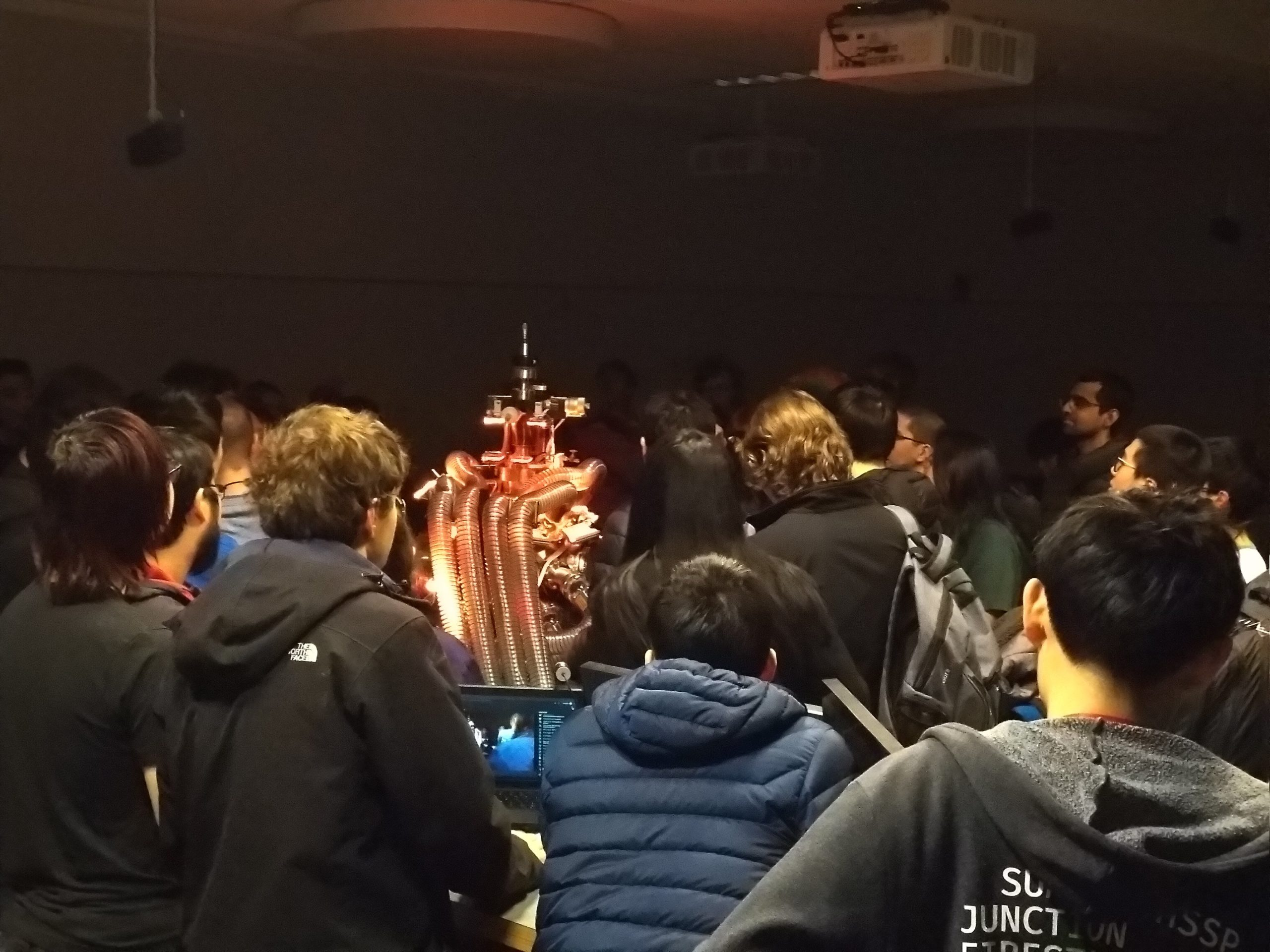 a bunch of people crowding around this… machine glowing in different colors