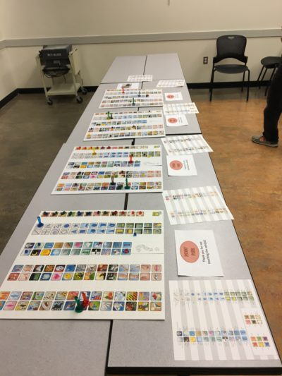 A long table on which several copies of the board game Concept are laid out.