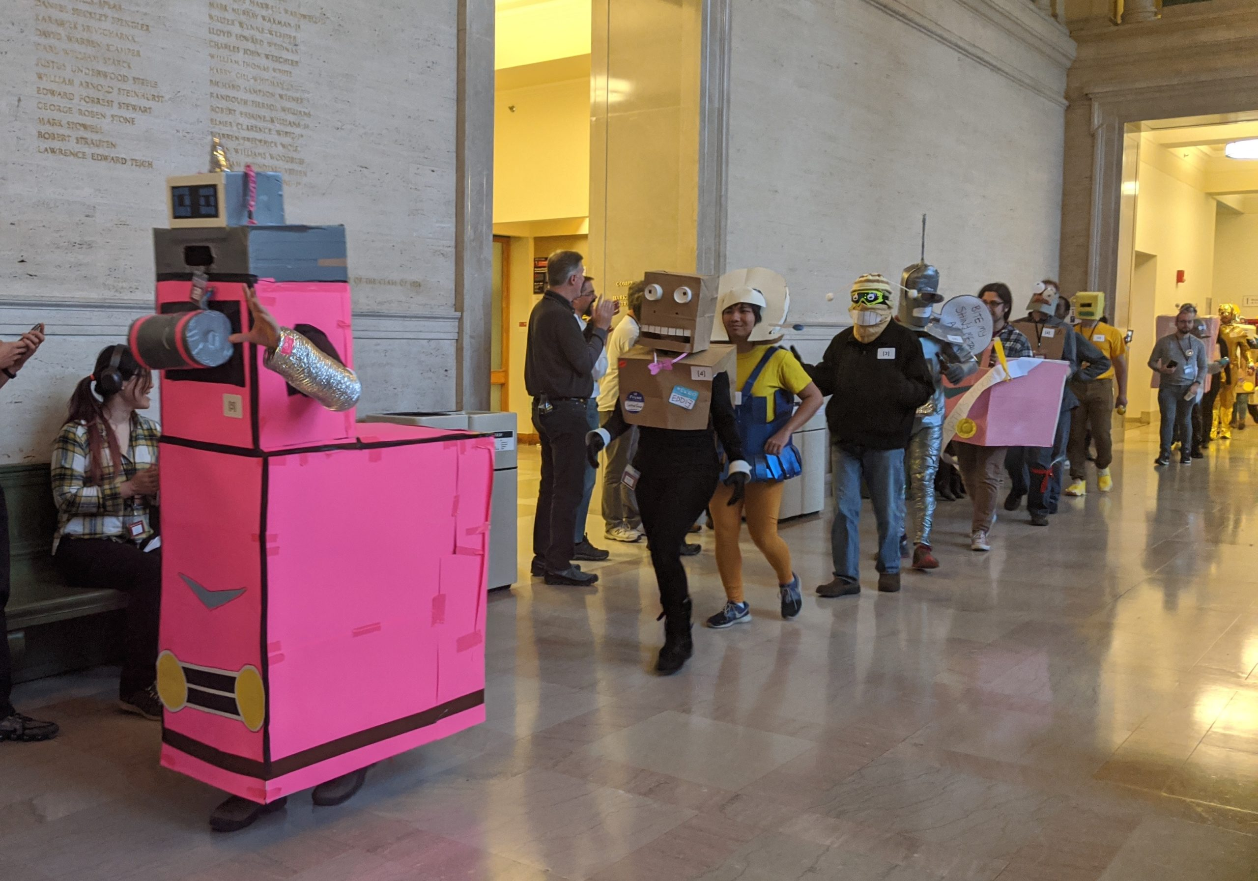 a bunch of people dressed as futurama robots parading down lobby 10