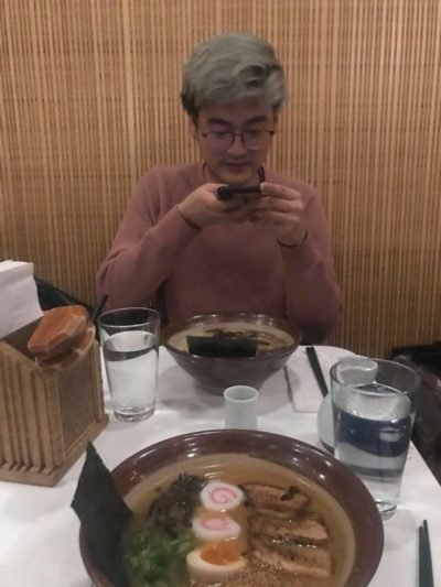 a picture of joon taking a picture of ramen