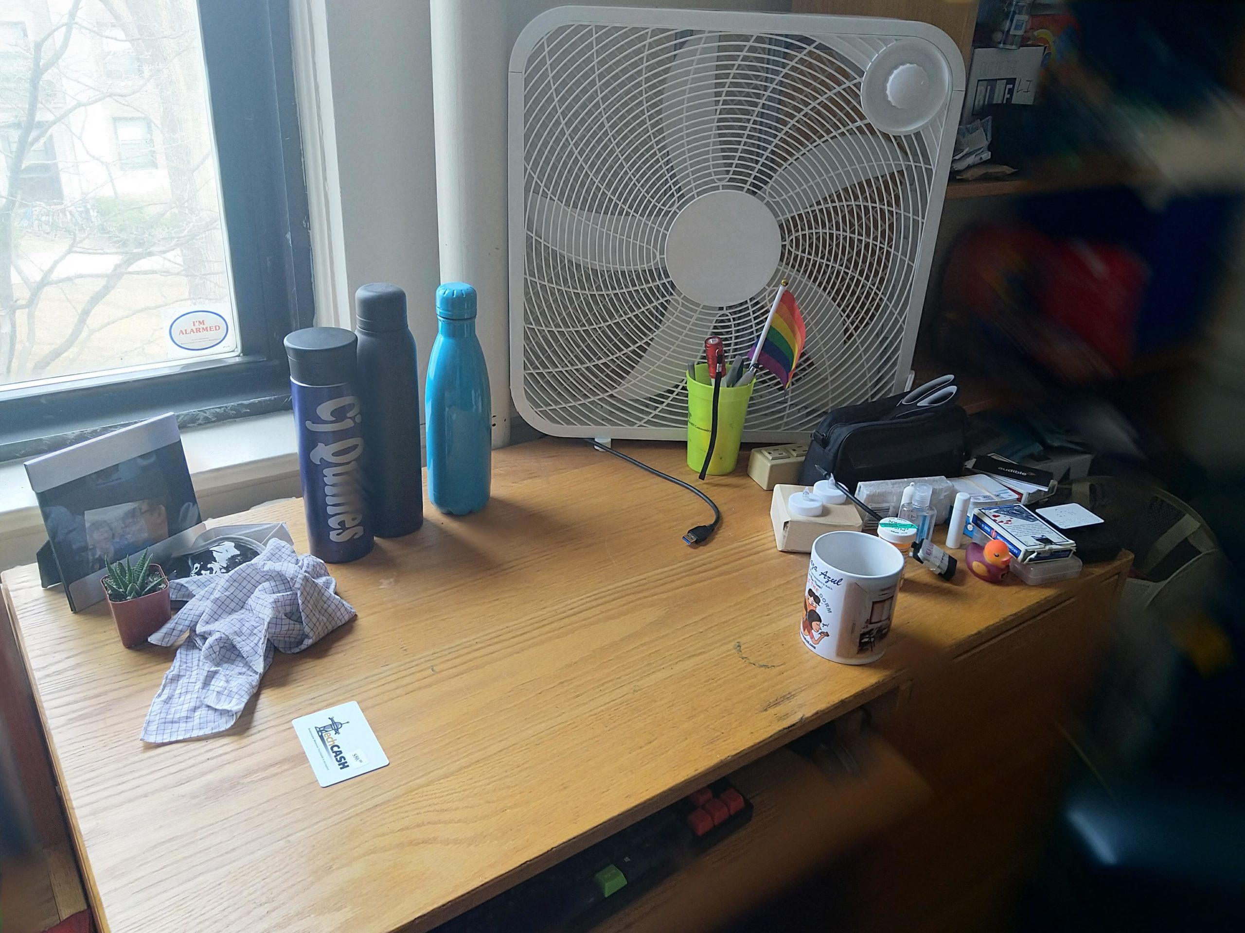 my desk. there's a box fan, three water bottles, a mug, a keyboard.