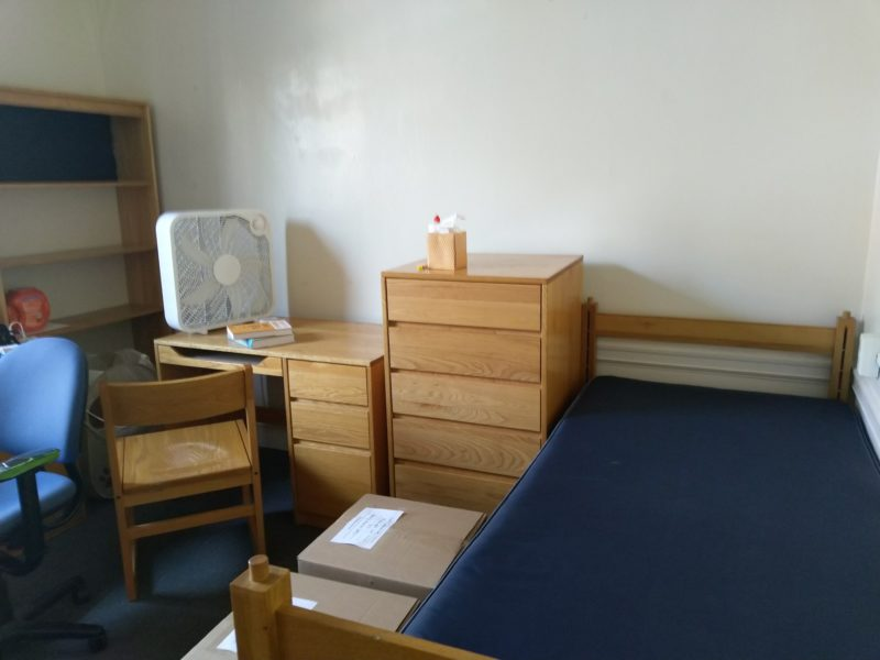 a bare mattress, an empty desk, two boxes on the floor