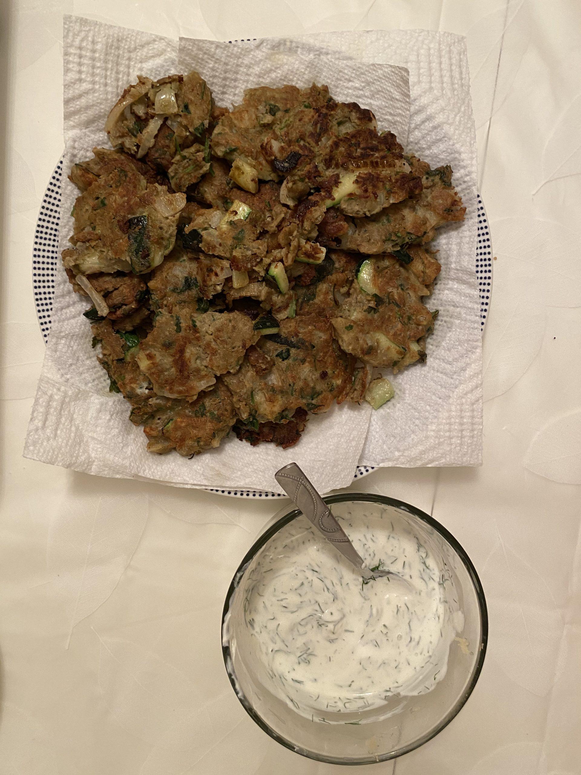 lentil zucchini fritters next to a bowl of yogurt sauce