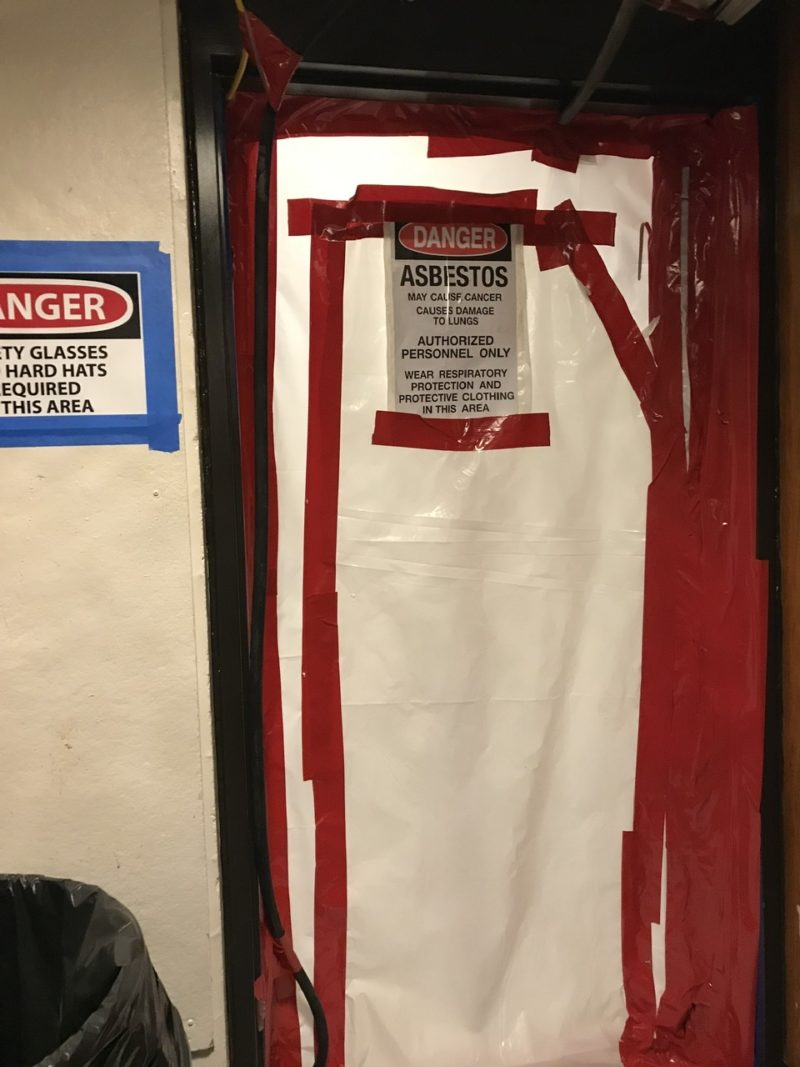 asbestos warnings posted in a construction area