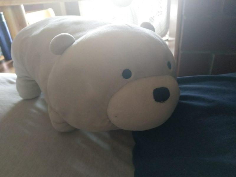 ice bear (a stuffed polar bear) on top of a bed