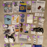 papers, receipts, knick knacks, show programs, playbills, movie tickets, and other trinkets laid out on…