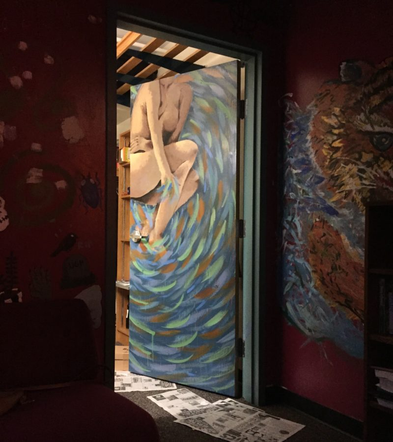 a photo of my door, with a woman surrounded by swirls painted on it