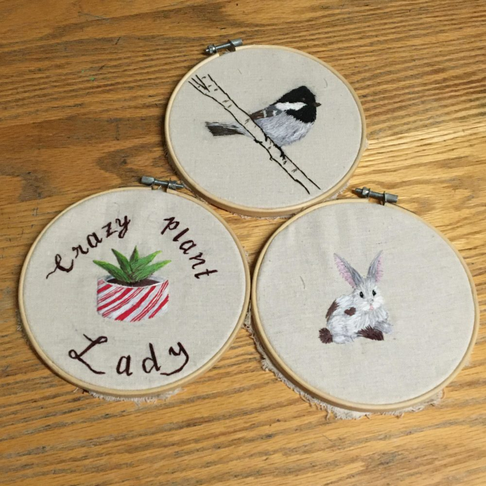 3 embroidery hoops with a bird, plant, and rabbit embroidered