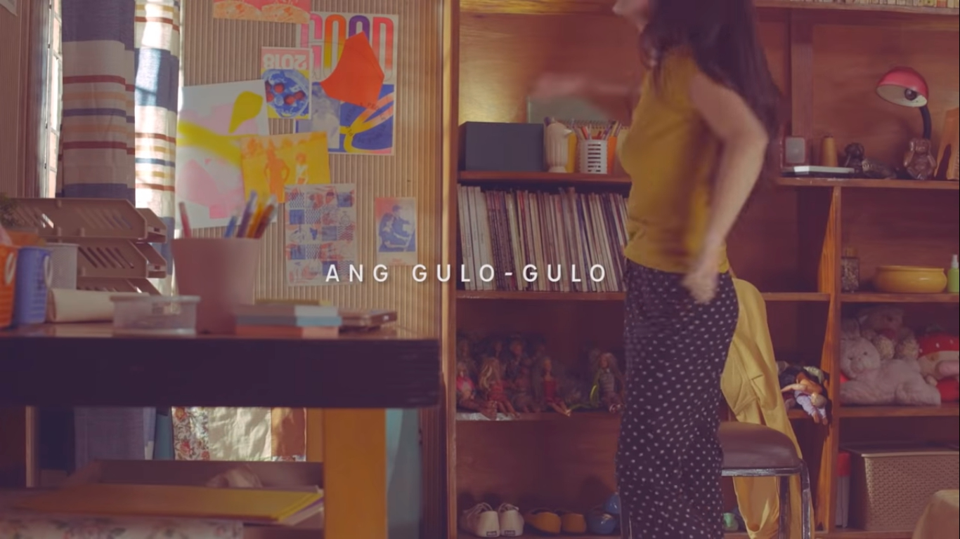 """screen capture from the alam mo ba? music video linked later in the post. person dancing in a messy bedroom. overlaid text says """"ang gulo-gulo"""""""