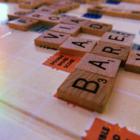 A close-up view of a scrabble board, focusing on the word