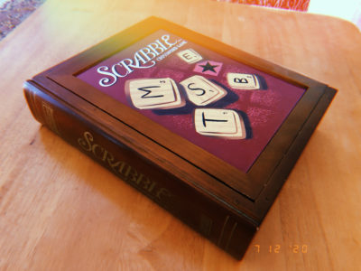 A wooden box holding the board and pieces of the scrabble game.