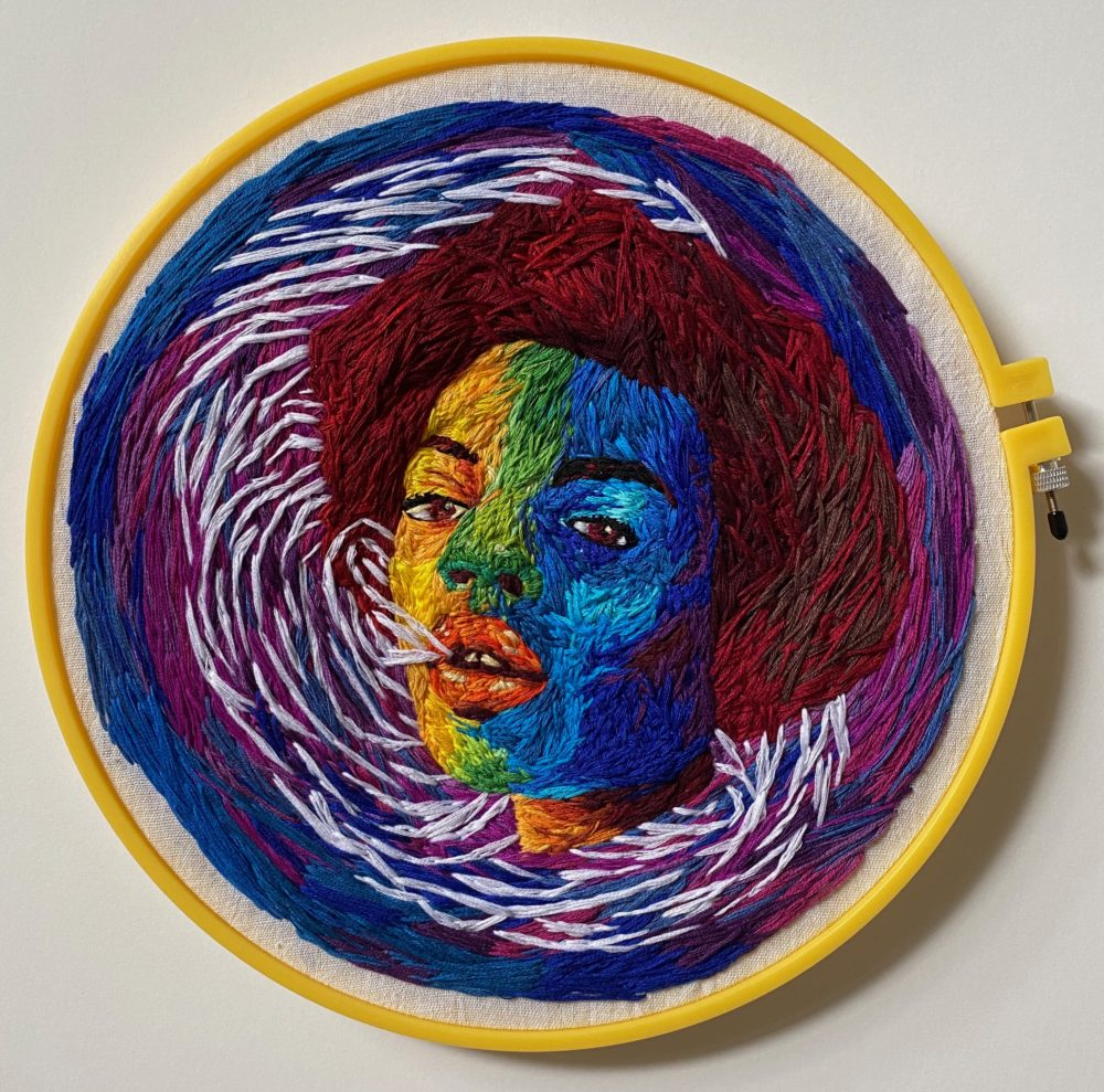 An embroidery hoop with a colorful face embroidered.