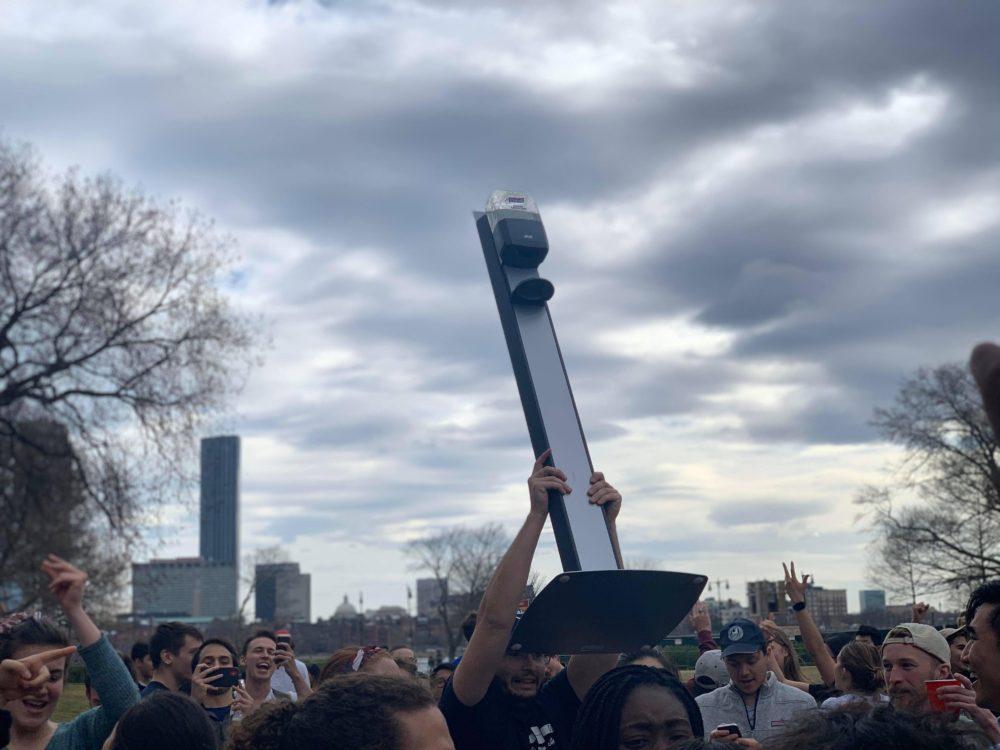 an MIT student lifts a purell dispenser into the air