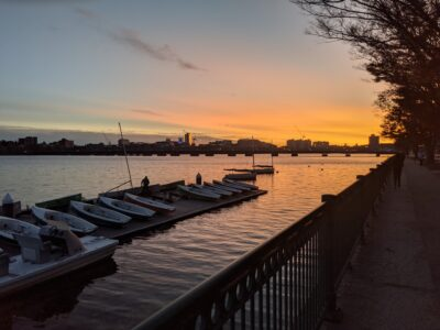 sunset over boats on the charles river