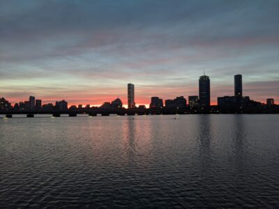 orange starting to bloom over the boston skyline, reflecting in the charles