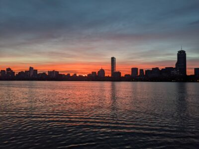 orange surrounds the boston skyline reflected in the charles river