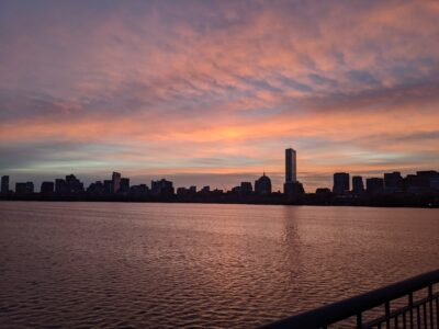 a spot of light shines up into pink clouds as the sun rises over boston