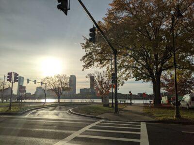 sun shines through clouds over boston skyline