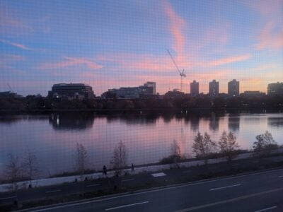 boston university skyline with pink clouds reflected on the charles at sunset