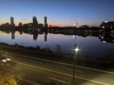boston skyline with pink clouds reflected in the charles at sunset