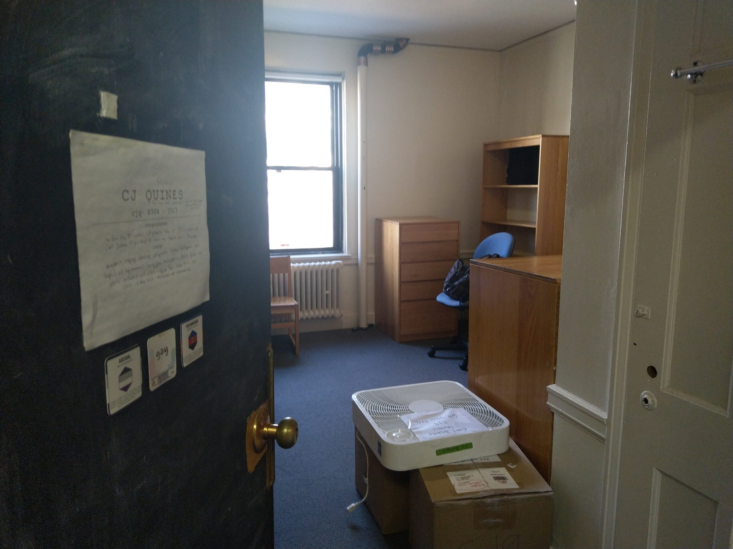 my room in east campus, empty, with two boxes on the floor