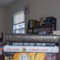 stack of books: The Invisible Life of Addie LaRue by VE Schwab, Black Skin, White…