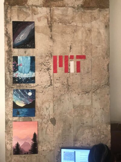 image of apartment wall with four paintings and an mit logo