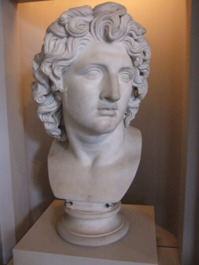 Marble bust of Alexander the Great, with a sharp nose and curly hair.