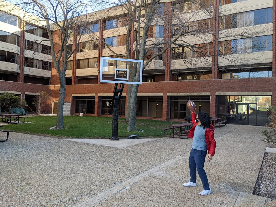 me posing to throw a football through a basketball hoop