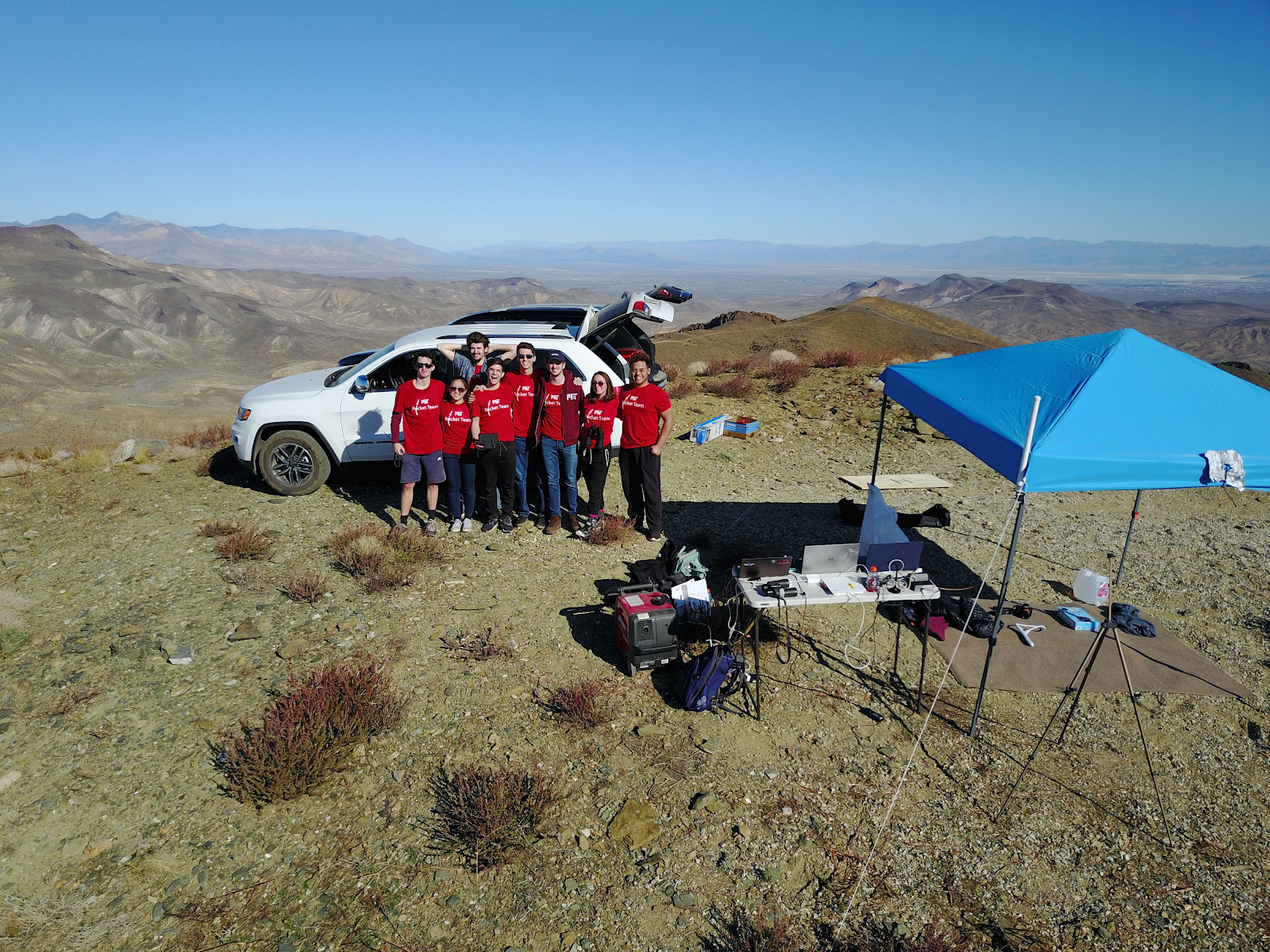 another group picture of the rest of Rocket Team standing in front of a car near an Avionics table and tent on a mountaintop in the Mojave Desert