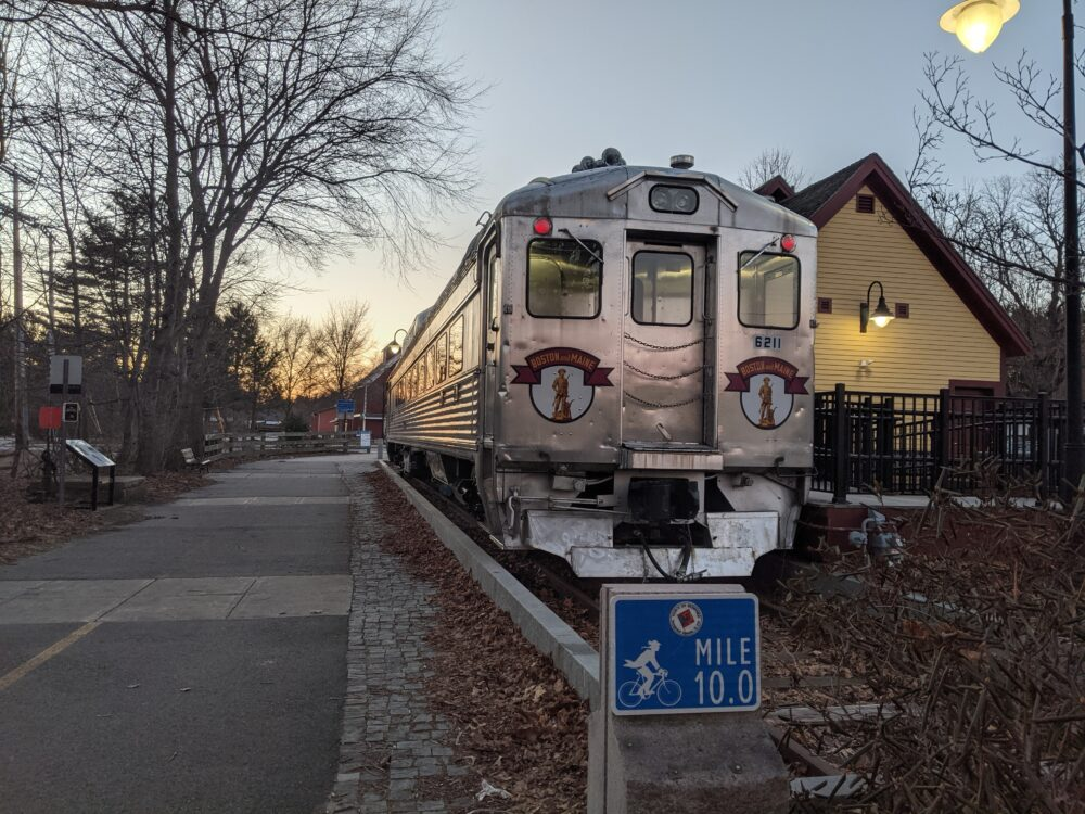 train at the end of bike path at sunset with 10 mile marker