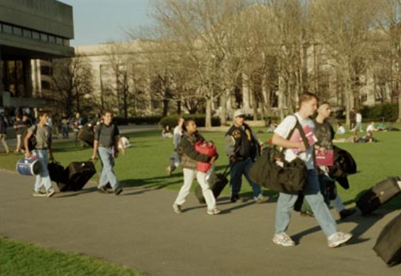 students walking across kresge lawn carrying bags