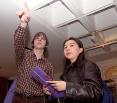 two people. left person points upward out of frame. right person holds a purple folder.