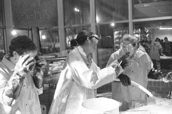 three people in lab coats standing over a tub. one person is feeding another person what is presumably ice cream.