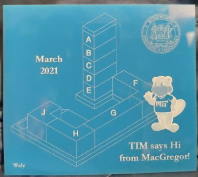 a laser cut blue acrylic with macgregor and tim the beaver on it