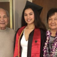 me wearing my graduation robe and cap with my grandparents