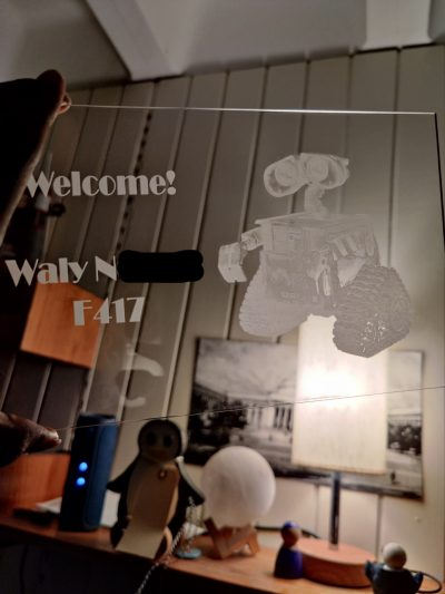 a clear laser cut acrylic with wall-e and welcome! on it