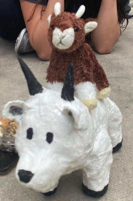 picture of a white model goat made of papier mache and a small stuffed animal goat stacked on top of it