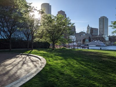 picture of green space in front of water and boston skyline at sunset