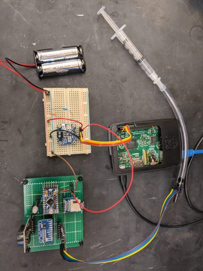 image of 3 circuit boards, connected with colored wires, and a small syringe