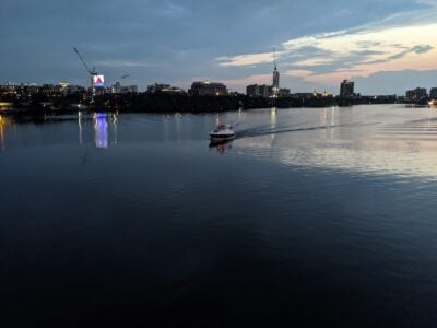 boat moving across the Charles River at sunset